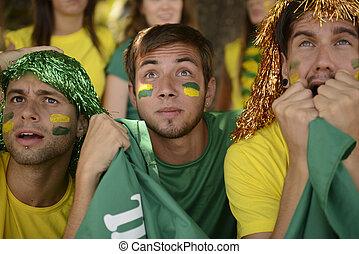 Brazilian sport soccer fans looking at the screen. -...
