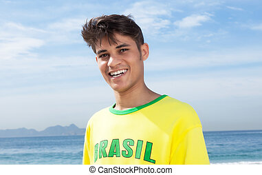 Brazilian sports fan at beach laughing at camera