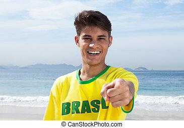 Brazilian sports fan at beach pointing at camera