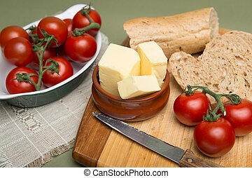 Bread and butter/Delicious organic home-made bread and butter with ripe tomatoes on wooden board