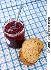 bread and jar with raspberry jam on blue tablecloth