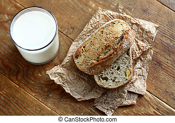Bread and milk - Top view on cut in halves whole grain bread...