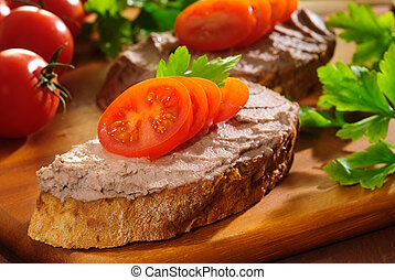 Liver pate with cherry tomatoes and herbs on a wooden chopping board