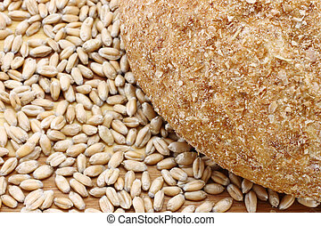 Bread and wheat seeds close-up on a wooden background