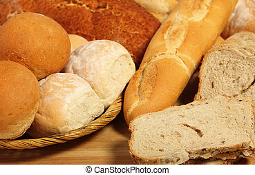 Bread board and breadbasket - A breadbasket with rolls on a...