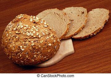 bread - Bread on cutting board is on wooden table.