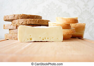 Bread cut by chunks and cheese on a wooden board