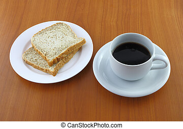 Bread dish and coffee on wooden table.