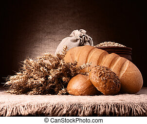 Bread, flour sack and ears bunch still life on rustic ...