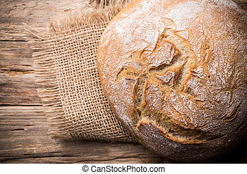 Fresh bread on a wooden background. Studio photography.