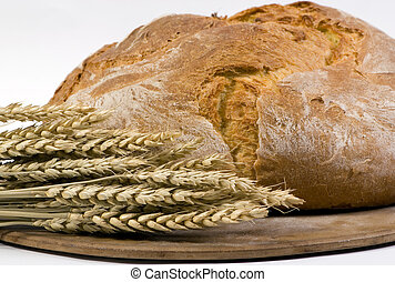 Bread Loaf with wheat on pan 3/4 shot - A crusted loaf of...