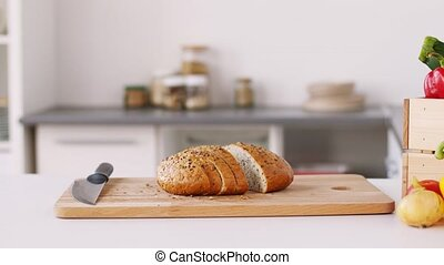 bread on cutting board and vegetables at home - food and...