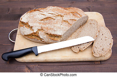 Bread on cutting board with knife on wooden table