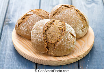 bread on wooden dish on blue background