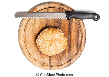 Bread roll covered with sesame seeds on cutting board with knife, typical German breakfast food. Studio shot, cutout, isolated on white background.