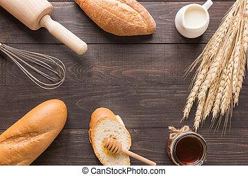 Bread rolls, milk, honey jar, wheat on wooden background