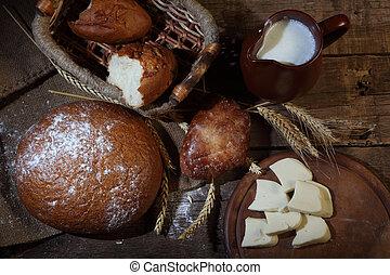 Bread round pshenichno - rye, milk in a jug and cheese
