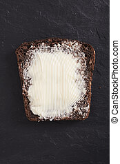 bread slice - whole whaet bread with butter over dark...