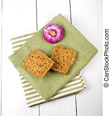 Bread slices and onion on wooden background
