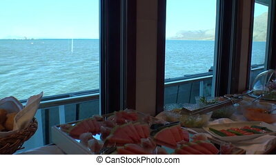 Bread, watermelon, lettuce and other food on the ship with a view of the ocean.
