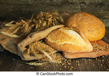 bread, wheat, ears of corn on a wooden background