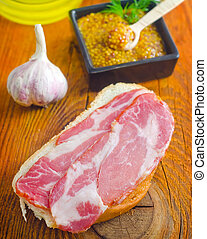 Bread with bacon on the wooden board