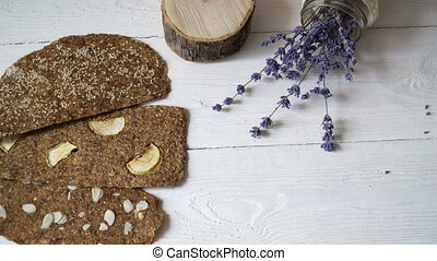 Bread with flaxseeds and almonds on a white wooden...