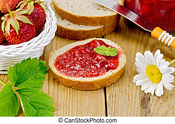 Bread with strawberry jam and chamomile on board