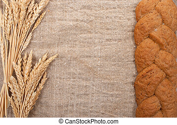 Bread with wheat  ears  on burlap background