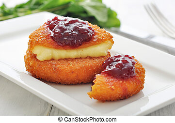 Breaded and baked camembert with cranberry sauce on white...