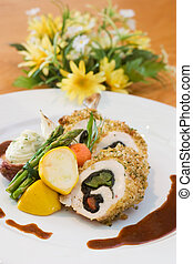 Breaded chicken slices stuffed with sweet peppers and served with asparagus and vegetables