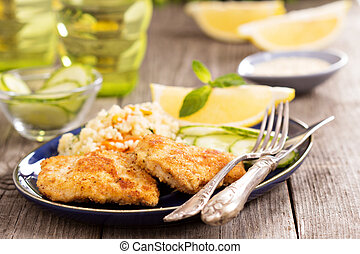 Breaded chicken fillet with couscous and lemons