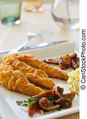 Breaded chicken breast fillet, served with tomato salad and...