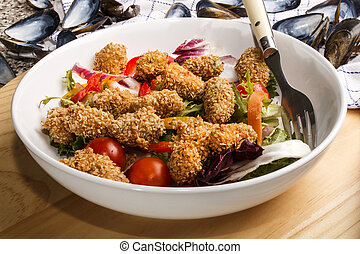breaded mussels with fresh salad in a deep dish