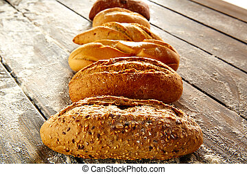 Breads varied in a row on rustic wood and flour - Breads ...