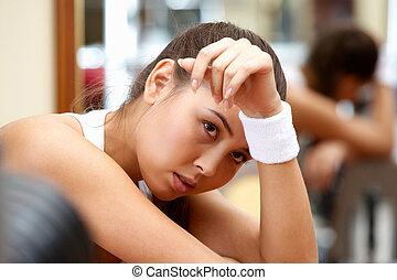Portrait of tired brunette having rest in short break after workout