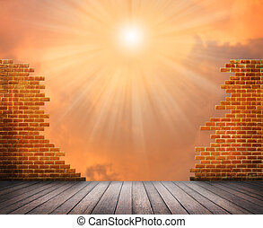 Break brick wall with sunlight ray and orange clouds sky background