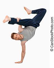 Break dancer doing an one handed handstand against a white...
