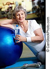 Break in gym  - Senior woman having break after exercises
