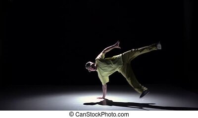 Breakdance dancer in yellow suit continue dance on black, shadow, slow motion