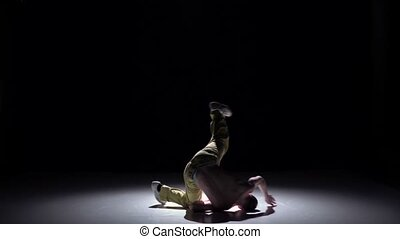 Breakdance dancer man in yellow trousers with torso continue dance on black, shadow, slow motion