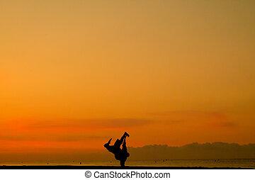 breakdance on the beach at sunset