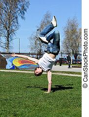 Breakdancer doing a flip on the grass.