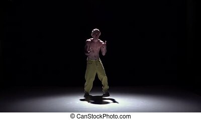 Breakdancer man in yellow trousers doing handstand on black, shadow, slow motion