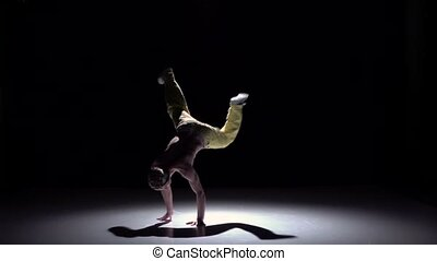 Breakdancer man in yellow trousers starts doing handstand on black, shadow, slow motion