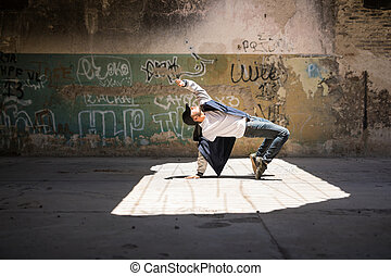 Breakdancer performing in an urban setting - Wide view of a...
