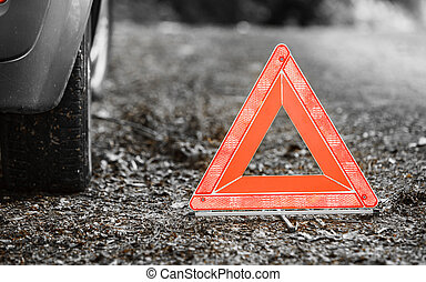 Car transportation. Breakdown of car transporation. Closeup of red warning triangle sign symbol on the forest road.