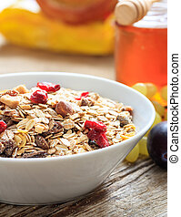 Breakfas bowl with muesli, fruits and nuts on a table, close up view