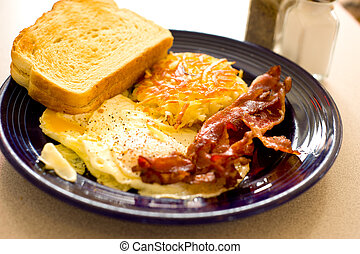A savory American breakfast at a restaurant with egg, bacon, hashbrown and toast on a blue plate. Very shallow depth of field