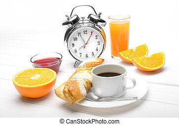 Breakfast and alarm clock. Coffee, croissant, juice and alarm clock on the table. Focus on the clock.